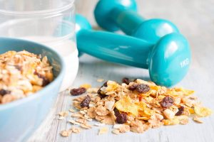 Diet and fitness concept with dumbbells and muesli closeup